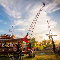 Pyrobar at sunset with aerialist performing on aerial rigged from crane.